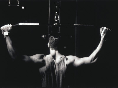 Rear View of a Young Man Exercise on a Lateral Pull-Down Weight Machine Photographic Print