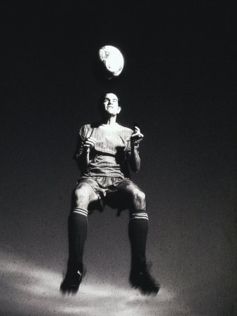 Low Section View of a Soccer Player Jumping in Mid Air to Head a Soccer Ball Photographic Print