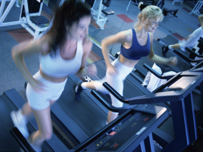 High Angle View of Two Young Women Running on Treadmills in a Gym Photographic Print