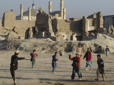 Afghan Boys Play Soccer Near a Mosque and Ruined Buildings During the Early Morning Photographic Print