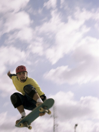 Low Angle View of a Young Man Skateboarding in Mid Air Photographic Print