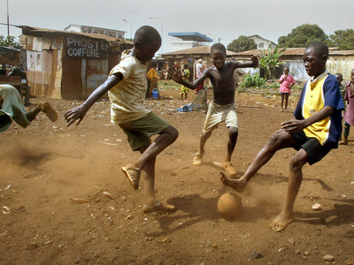 Young Children Play Soccer on a Dirt Pitch by the Side of Railway Tracks Photographic Print