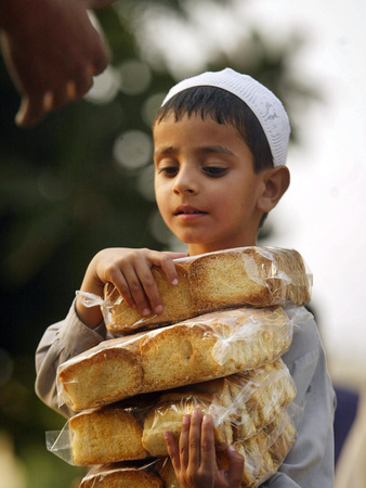 A Boy Carries Rusk as He Assists Others to Send a Consignment of Relief Supplies to Uri Photographic Print