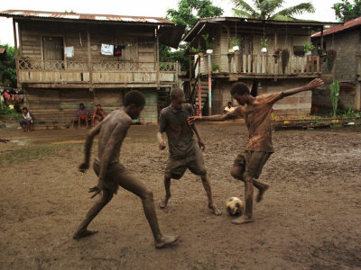 A Group of Panamanian Youths Slide Through the Mud During a Pick-Up Game of Soccer Photographic Print