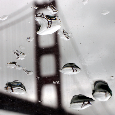 Rain Drops are Shown on a Car Windshield with the Golden Gate Bridge in Background Photographic Print