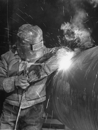 Worker Welding Pipe Used in Natural Gas Pipeline at World's Biggest Coal Fueled Generating Plant 写真プリント : マーガレット・バーク=ホワイト