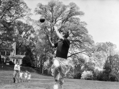 Robert F Kennedy and Family Outside Playing Football with His Brother Senator John F. Kennedy Photographic Print by Paul Schutzer