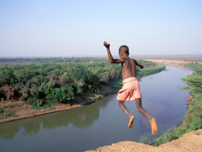 Karo Boy Leaps Off a Cliff Over the Omo River, Ethiopia Photographic Print by Janis Miglavs