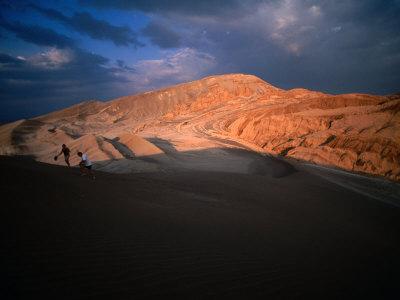 Couple of Hikers Walking Through Shadows at Dusk, Valle De La Luna, Chile Lámina fotográfica por Aaron McCoy