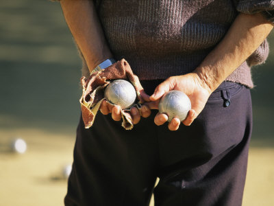 A Man Holding Two Balls Waiting His Turn to Play Bocci Photographic Print by Michael Melford