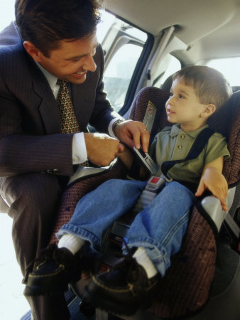 Mid Adult Man Strapping His Son into a Car Photographic Print