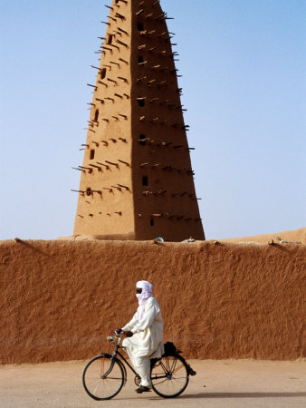 Robed Tuareg Man Cycling Past Minaret of Mud-Brick Grande Mosquee, Agadez, Niger Fotografisk tryk af Pershouse Craig