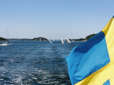 Swedish Flag with Sailboats in the Background, Stockholm Archipelago, Sweden Photographic Print