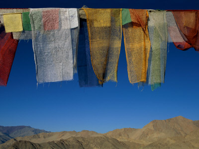 A Line of Multi-Colored Prayer Flags Sway in the Gentle Breeze in Ladakh Photographic Print by Barry Tessman