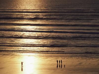 A Setting Sun Casts Golden Light over a Sandy Beach Photographic Print by Robert Madden