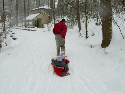Man Pulling Two Children on a Sled Through the Snow Photographic Print by Todd Gipstein