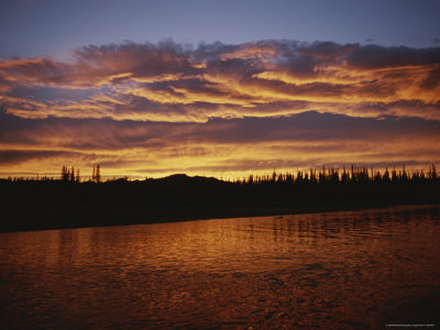 An Intense Sunset Colors Clouds and the Water of the Mackenzie River Photographic Print by Raymond Gehman