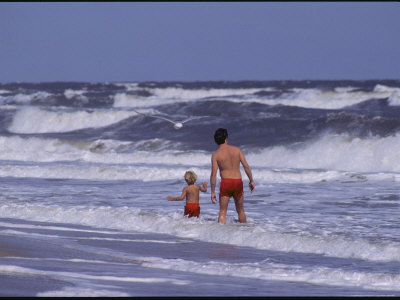 A Man and Child Play in the Assateague Island Surf Photographic Print by Medford Taylor