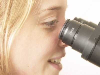Woman Looking Into Microscope Photographic Print