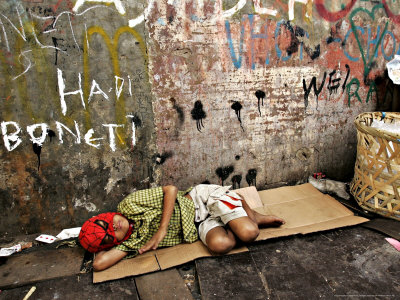 An Indonesian Boy Wearing a Spiderman Mask Sleeps on a Piece of Cardboard Photographic Print by Ed Wray