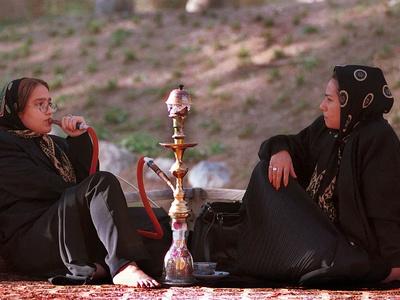 Two Unidentified Iranian Women Smoke a Water Pipe Photographic Print