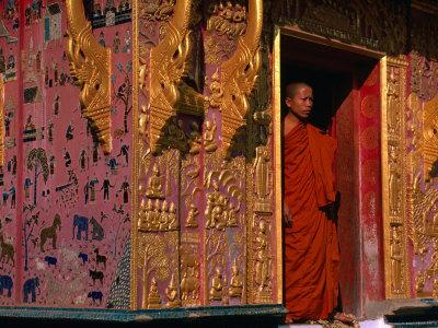 Buddhist Monk Standing in Doorway of Wat Xieng Thong, Luang Prabang, Laos Photographic Print by John Banagan