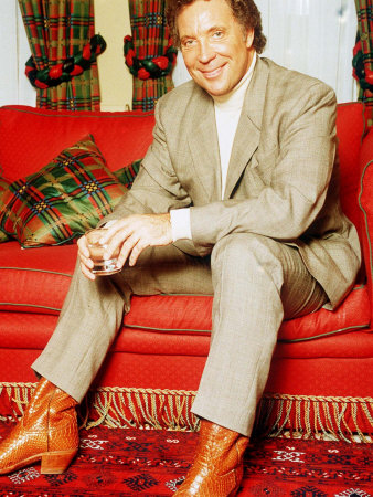 tom-jones-sitting-on-red-sette-pale-suit
