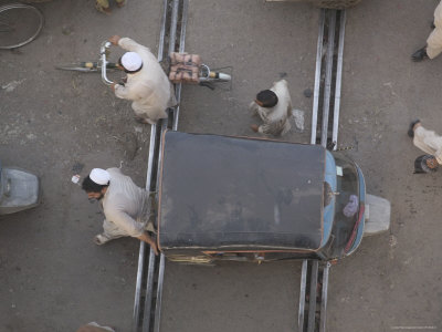Overhead View of Men Pushing Rickshaw across Train Lines Lámina fotográfica