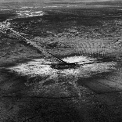 First Atomic Bomb's Dark Crater Surrounded by Glass Created by Heated Sand from Explosion Photographic Print by Fritz Goro