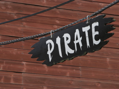 Pirate Sign Hanging Near a Wooden Wall Photographic Print