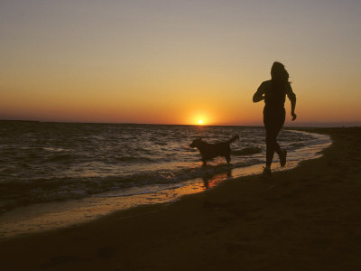 Woman and Her Dog Running Along Currituck Sound Beach at Sunset, Nags Head, North Carolina Photographic Print by Skip Brown