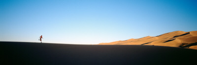 Low Angle View of a Woman Running in the Desert, Great Sand Dunes National Monument, Colorado, USA Photographic Print by  Panoramic Images