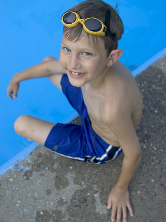 Portrait of 9 Year Old Boy Sitting at the Edge of the Swimming Pool, Kiamesha Lake, New York, USA Photographic Print by Paul Sutton