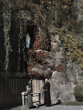 Two People Stand in Front of a Replica of the Grotto of Lourdes Fotografisk trykk