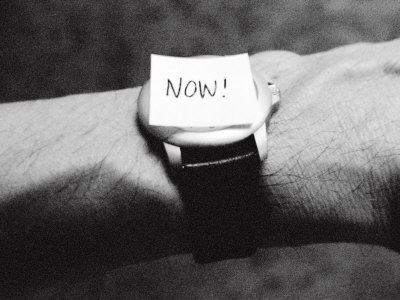 The Word Now as a Reminder Attached to a Watch on a Male Arm Photographic Print by Winfred Evers