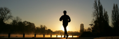 Jogger Silhouetted Against the Rising Sun as He Runs Past the Serpentine Lake in Hyde Park, London Photographic Print