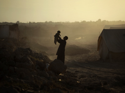 Displaced Man Holds His Baby Next to His Tent in Jalozai Refugee Camp Near Peshawar, Pakistan Photographic Print