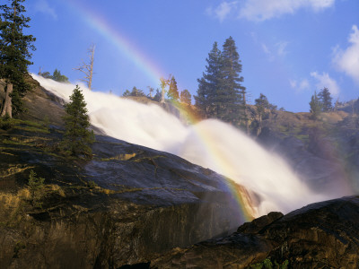 Mist of water in Waterwheel Falls produce a rainbow over the mountains Yosemite waterfall photo by Jeff Foott