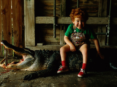 A Five Year Old Boys Sits on a Dead 10-Foot Long Alligator Photographic Print by Joel Sartore