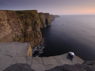 A Couple Lies on Rocks Overlooking the Cliffs of Moher and the Sea Photographic Print by Jim Richardson