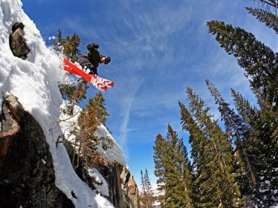 Skier Jumping Off Small Cliff at Brighton Ski Resort Fotografisk tryk af Paul Kennedy