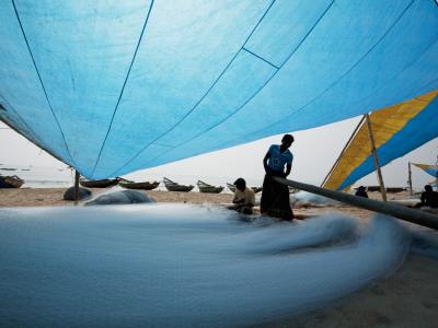 Fishermen Repairing their Nets under Shade of Sail Photographic Print by April Maciborka