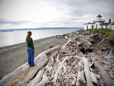 Woman Standing on Driftwood and Looking Towards Discovery Park Lighthouse Photographic Print by Micah Wright