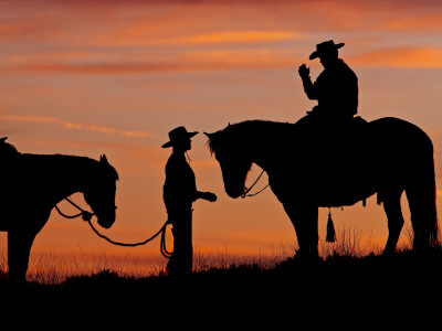 Cowboy and Cowgirl Silhouetted on a Ridge in the Big Horn Mountains, Wyoming, USA Photographic Print by Joe Restuccia III