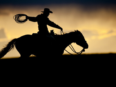 A Silhouetted Cowboy Riding Alone a Ridge at Sunset in Shell, Wyoming, USA Photographic Print by Joe Restuccia III