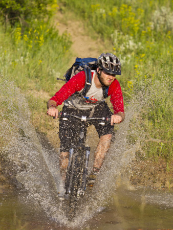 Mountain Biker Splashes Through Andrews Creek, Maah Daah Hey Trail in Medora, North Dakota, USA Photographic Print by Chuck Haney