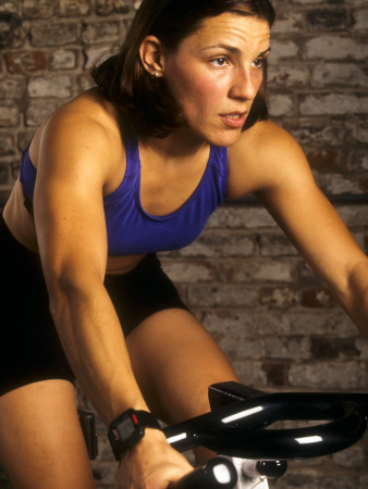 Young Woman Exercising on a Stationary Bike Photographic Print!