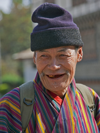 An Old Man at Trashigang Wearing the Traditional Gho Robe of All Bhutanese Men Photographic Print by Nigel Pavitt