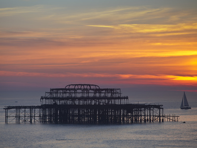 UK, England, Sussex, Brighton, Boat Sailing Past Remains of Brighton West Pier at Sunset Photographic Print by Jane Sweeney