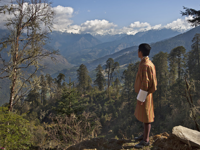 A Bhutanese Man in National Costume Views an Eastern Himalayan Mountain Range from the 11,000-Foot- Photographic Print by Nigel Pavitt